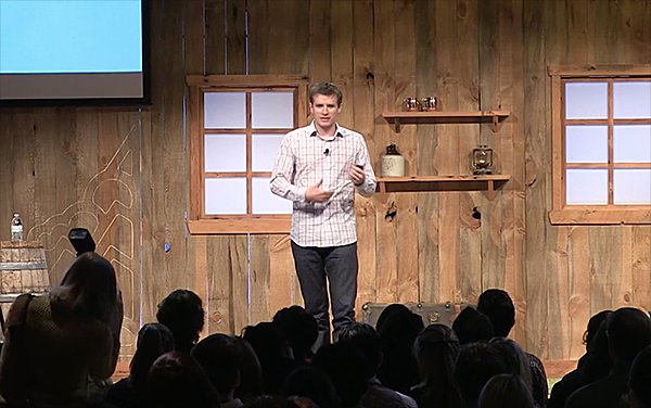 Nathan Barry presents his conference talk in front of a log cabin background at the Pioneer Nation conference.